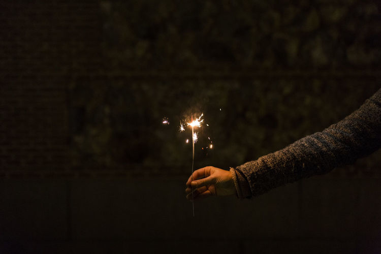Cropped hand of person holding sparkler at night