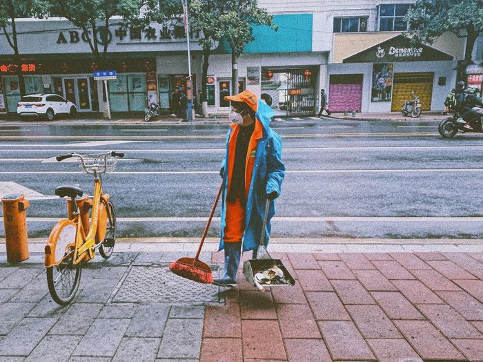 Man working on footpath by street in city