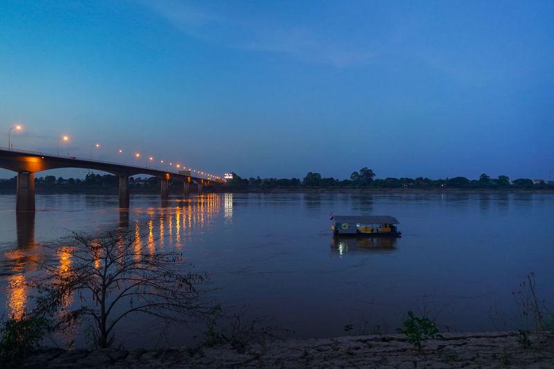 Bridge Over Lake Against Sky At Night