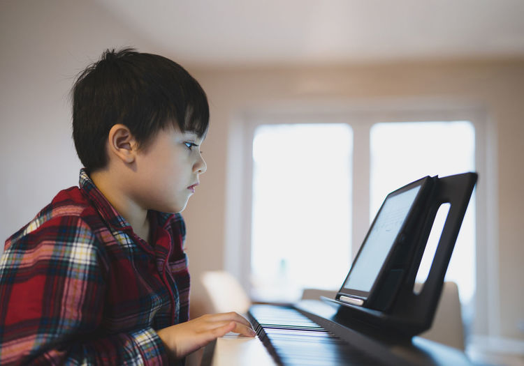 Portrait of kid playing piano, young boy learning music with an electric piano