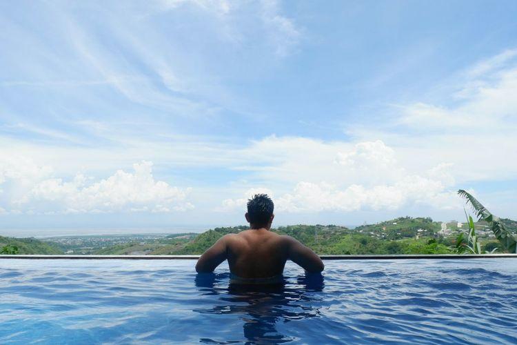 Full length of shirtless man in swimming pool against sea