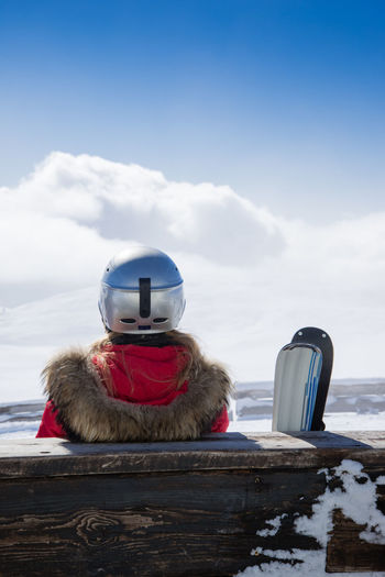 Rear view of person with snowboard sitting on bench against sky