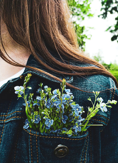 Midsection of woman with plants in pocket