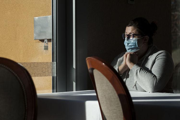 Portrait of woman sitting by window