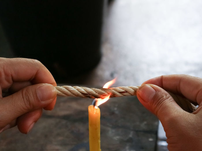Close-up of hand holding rope over burning candle