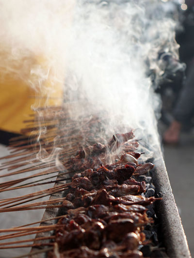 Close-up of meat on barbecue grill. the seller is grilled satay.
