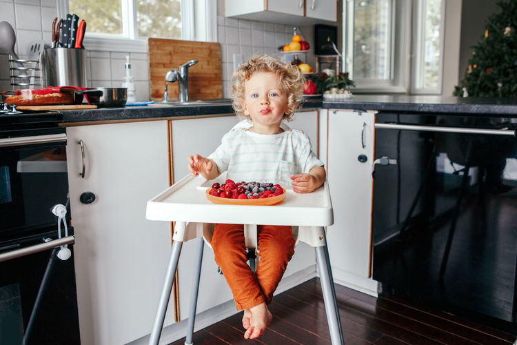 Baby boy eating ripe red fruits at home. supplementary healthy finger food for toddler kids.