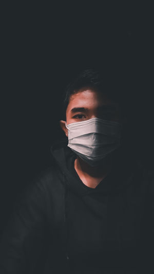 Close-up portrait of young man wearing mask against black background
