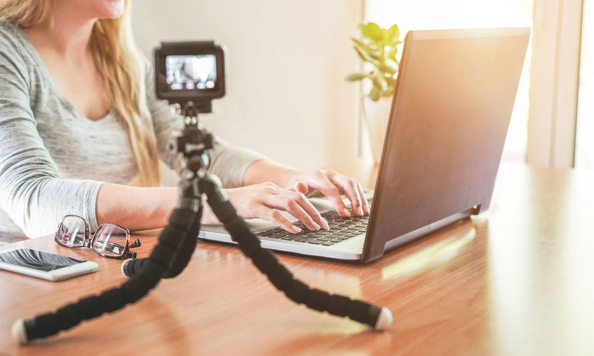 Midsection Of Young Woman Using Laptop On Table At Home