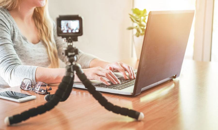 Woman blogger recording one video Camera Home Office Vlog Vlogger Young Blogg Blogger Computer Connection Desk Digital Indoors  Internet Job Laptop Live person Record Sitting Stream Table Technology Video Working