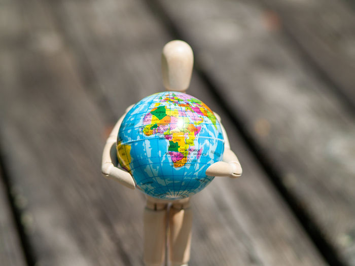 Close-up of wooden figurine holding globe on table