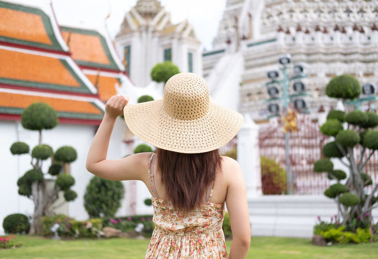 Rear view of young Asian woman traveling in Bangkok at Wat arun temple Bangkok Rear View Thailand Travel Travel Photography Wat Arun (Temple Of Dawn) Adult Architecture Building Exterior Built Structure Clothing Concept Focus On Foreground Hat Leisure Activity Lifestyles One Person Real People Rear View Straw Hat Sun Hat Travel Thailand Travel Destinations Traveler Women