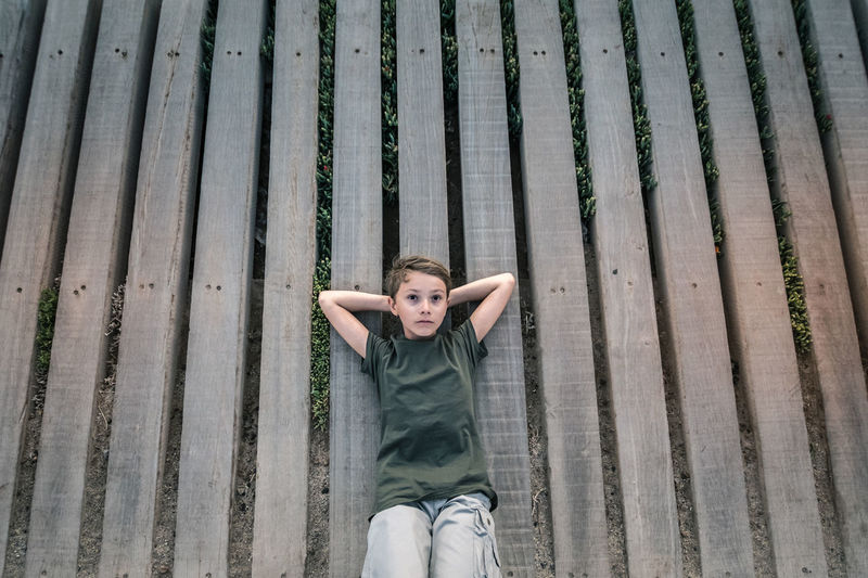 Beautiful blond child Brown eyes resting calm and peaceful lying on wooden planks floor arms crossed behind head green t-shirt succulents growing among nailed wooden planks. Young boy frontal portrait One Person Leisure Activity Real People Young Adult Front View Casual Clothing Three Quarter Length Lifestyles Day Sitting Looking At Camera Standing Portrait Emotion Young Women Young Men High Angle View Adult Human Arm