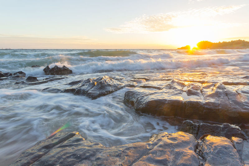 Scenic view of ocean waves at sunset