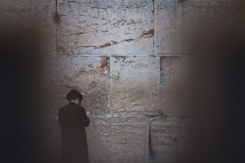 Rear view of man praying wailing wall