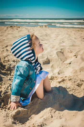 Girl sitting at beach with legs buried in sand
