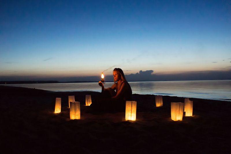 Woman sitting amidst lanterns at beach during dusk
