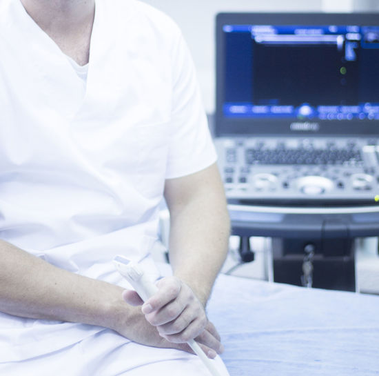 Midsection of doctor holding equipment while sitting on bed in hospital