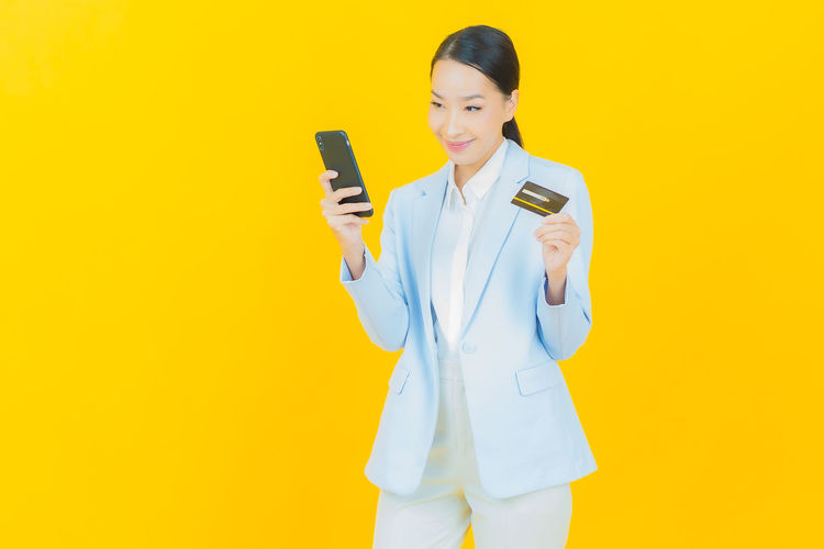 Young woman using smart phone against yellow background