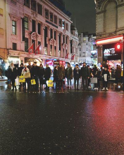 People walking on street by buildings at night