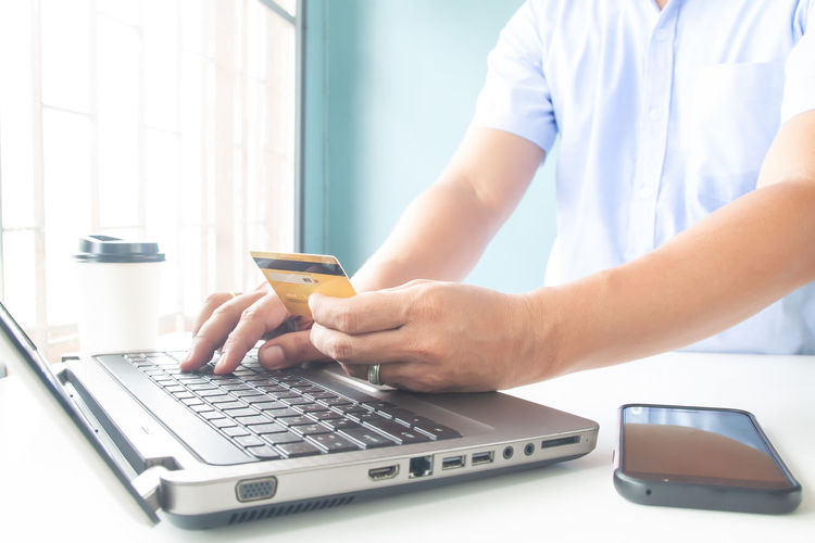 Online payment, Man's hands holding a credit card and using laptop for online shopping E-commerce Typing Cvv Monitor Wireless RISK Tablet Tax Information Data Communication Order Female Debit Smart Human Background Man Digital Keyboard Notebook Store Buy Home Purchase Bank Lifestyle Pay Laptop Mobile Phone Electronic Commerce Internet Finance White Woman Technology Holding Business Computer Hands Using Shopping Banking Payment Online  Card Credit