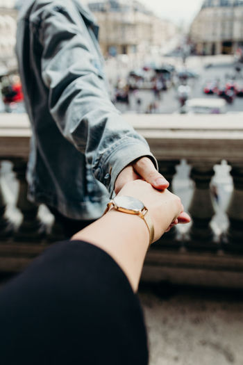 Midsection of woman holding hands with a man in paris