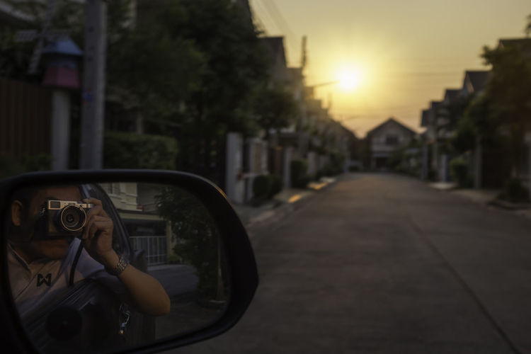 Reflection of man photographing car on side-view mirror