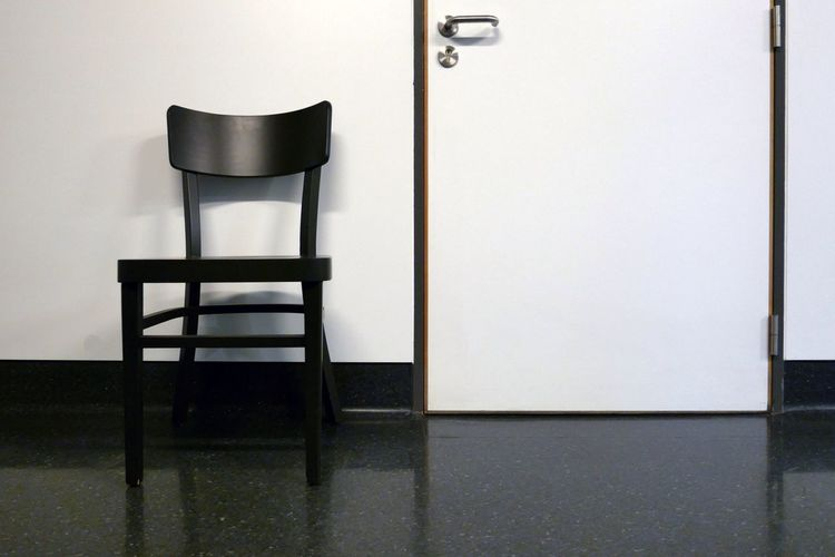 Empty chair by closed white door