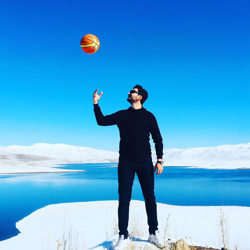 Full length of young man playing with basketball against lake during winter