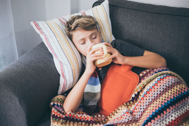 High angle view of ill boy having drink while lying on sofa at home