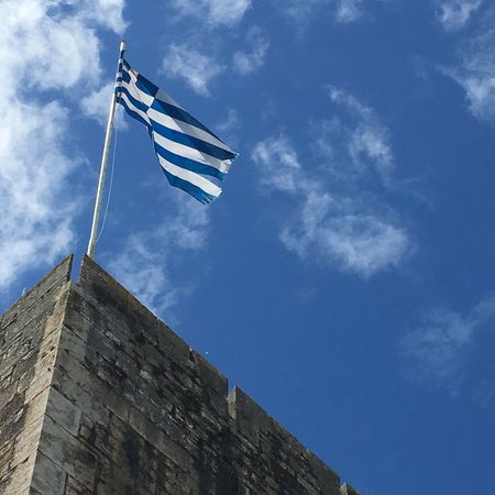 Greek flag flying in the wind atop the New Fortress, Corfu Town, Greece Ancient Building Architecture Blue Blue Sky Cloud Cloud - Sky Cloudy Corfu Town Culture Day Flag Pole Flying High Flying In The Wind Greek Flag Low Angle View Nature New Fortress No People On Top Outdoors Pole Sky Tall - High