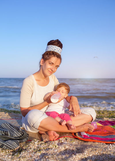 Mother on daughter on the travel vacation. Family leisure. Summer Sea Water Beach Childhood Young Child Baby Full Length Togetherness Sitting Two People Emotion Family Sky Holiday Bonding Babyhood Nature Innocence Daughter Horizon Over Water Family With One Child Nutrition Mother And Child Vacations