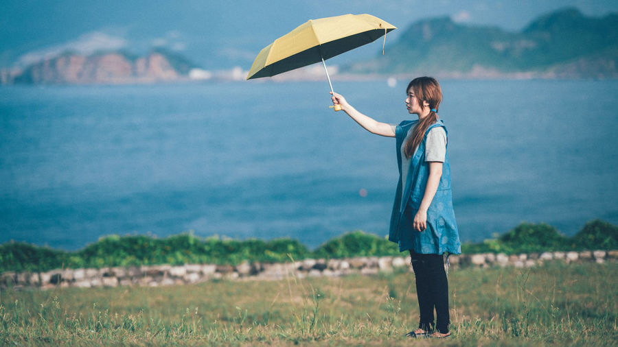 Side view of young woman holding umbrella while standing by lake