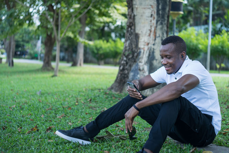 Full length of young man sitting on grass