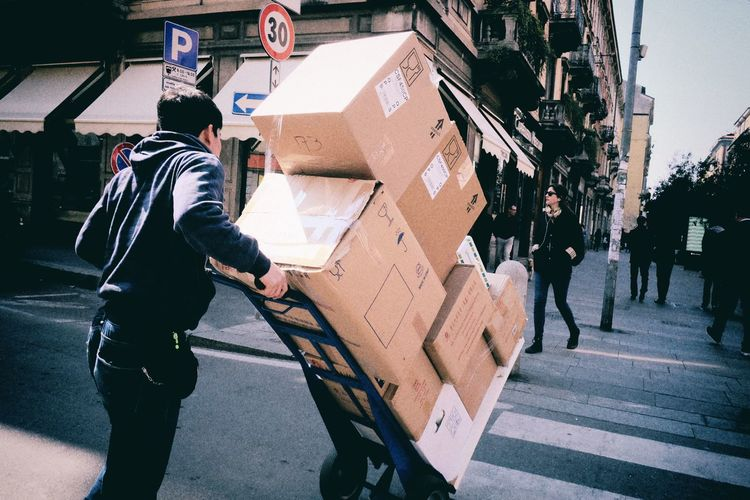 Man Pushing Cart With Cardboard Boxes On Street In City