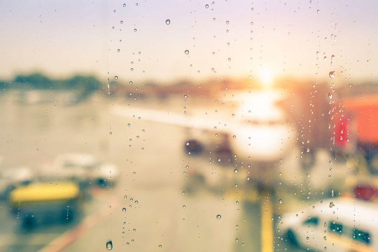 Abstract defocused bokeh of airplane at airport gate with sun coming out after the rain - Modern travel concept and wander lifestyle at sunset - Focus on raindrops with warm vintage filtered look Abstract Aerospace Air Aircraft Airline Airplane Airport Autumn Aviation Background Blurred Boarding Bokeh Business Charter Commercial Connection Defocused Drop Droplet Fall Filter Flights Flying Gate Glass Industry International Jet Outdoor Plane RainDrop Raining Rainy Season  Sunset Terminal Transport Transportation Travel Trip Vacation View Vintage Wanderlust Water Weather Wet Window Aeroplane