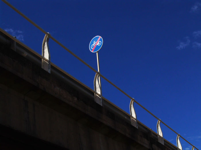 Low angle view of road sign on bridge