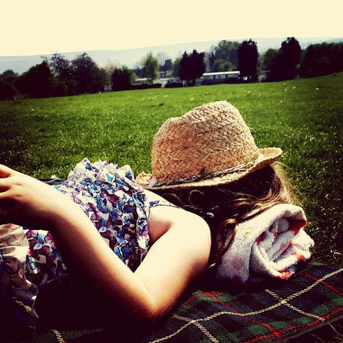 Midsection of woman with dog relaxing on grass