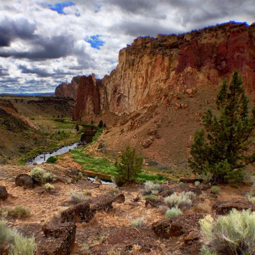 View of smith rock state park against cloudy sky