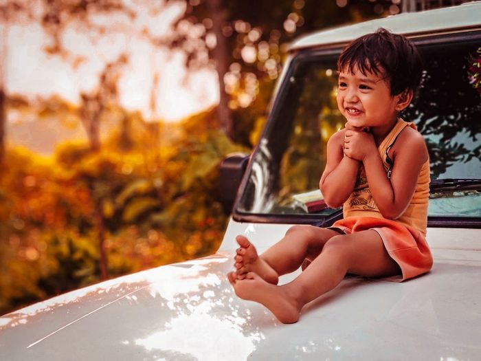 Full length of cute smiling girl looking away while sitting on vehicle hood during sunset