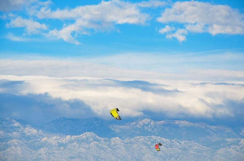 Paragliding over mountain against sky
