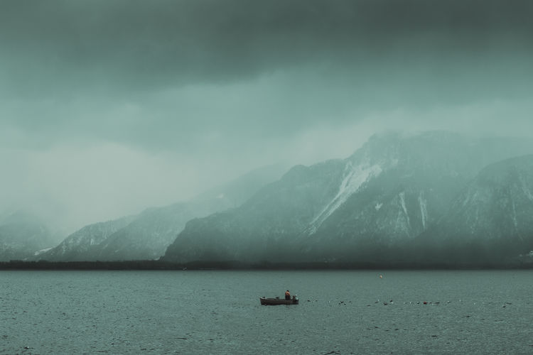 fisherman with boat alone on the lake Water Mountain Nature Boat Solitude Fishing Fisherman Lake Seagulls Back Tranquil Scene Scenics - Nature Travel Sea Tranquility Waterfront Mountain Range Outdoors Alone Foggy Fog