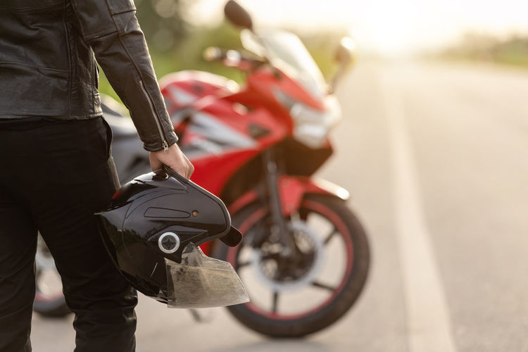 Rear view of man holding motorcycle