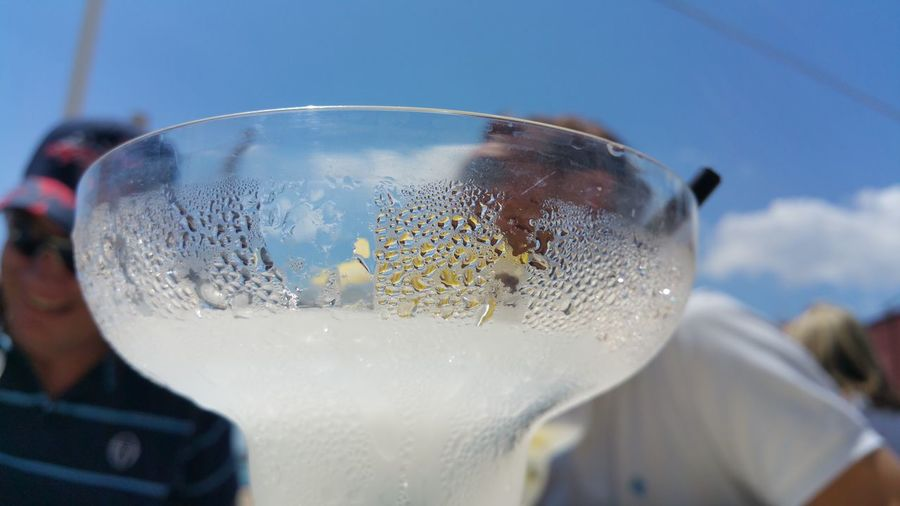 Close-up of condensed cocktail glass on sunny day