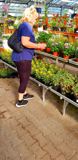 Client in a garden center looks for balcony plants while holding a flowerpot in her hand Real People One Person Plant Lifestyles Retail  Full Length Women Flowering Plant Store Rear View Leisure Activity Adult Business Flower Market Standing Growth Choice Small Business Outdoors Buying Retail Display