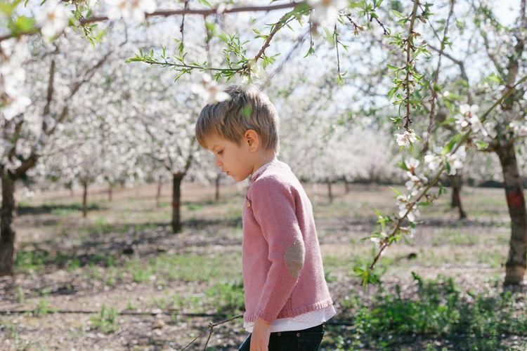 Cute Boy Standing On Field Against Trees