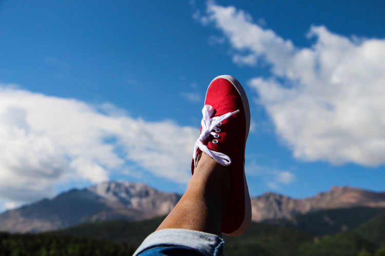 Low section of person wearing red shoes with feet up against mountains
