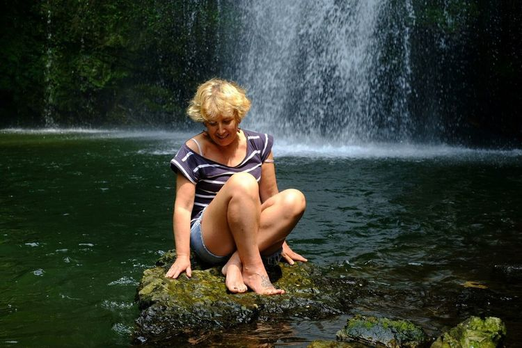 Full length of mature woman sitting on rock against waterfall