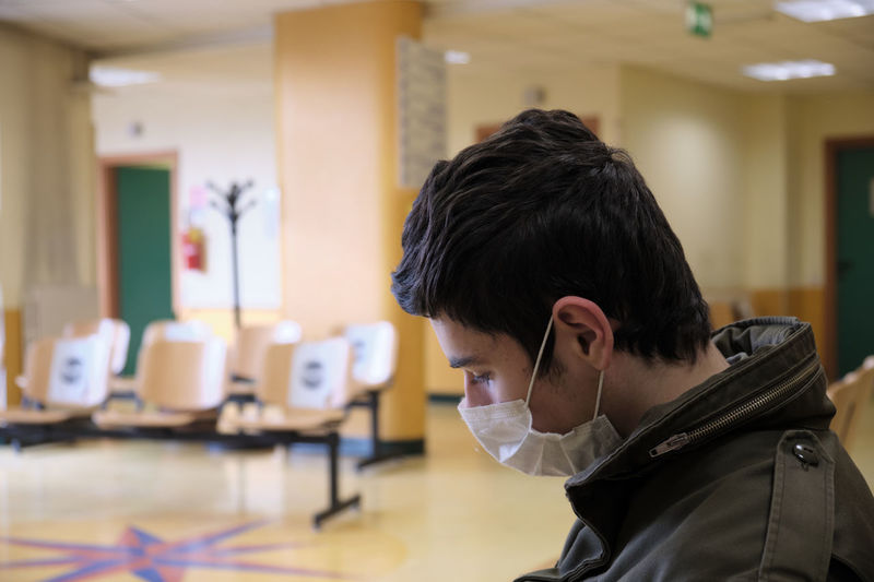 Caucasian boy wearing covid19 mask is waiting for hospital exams
