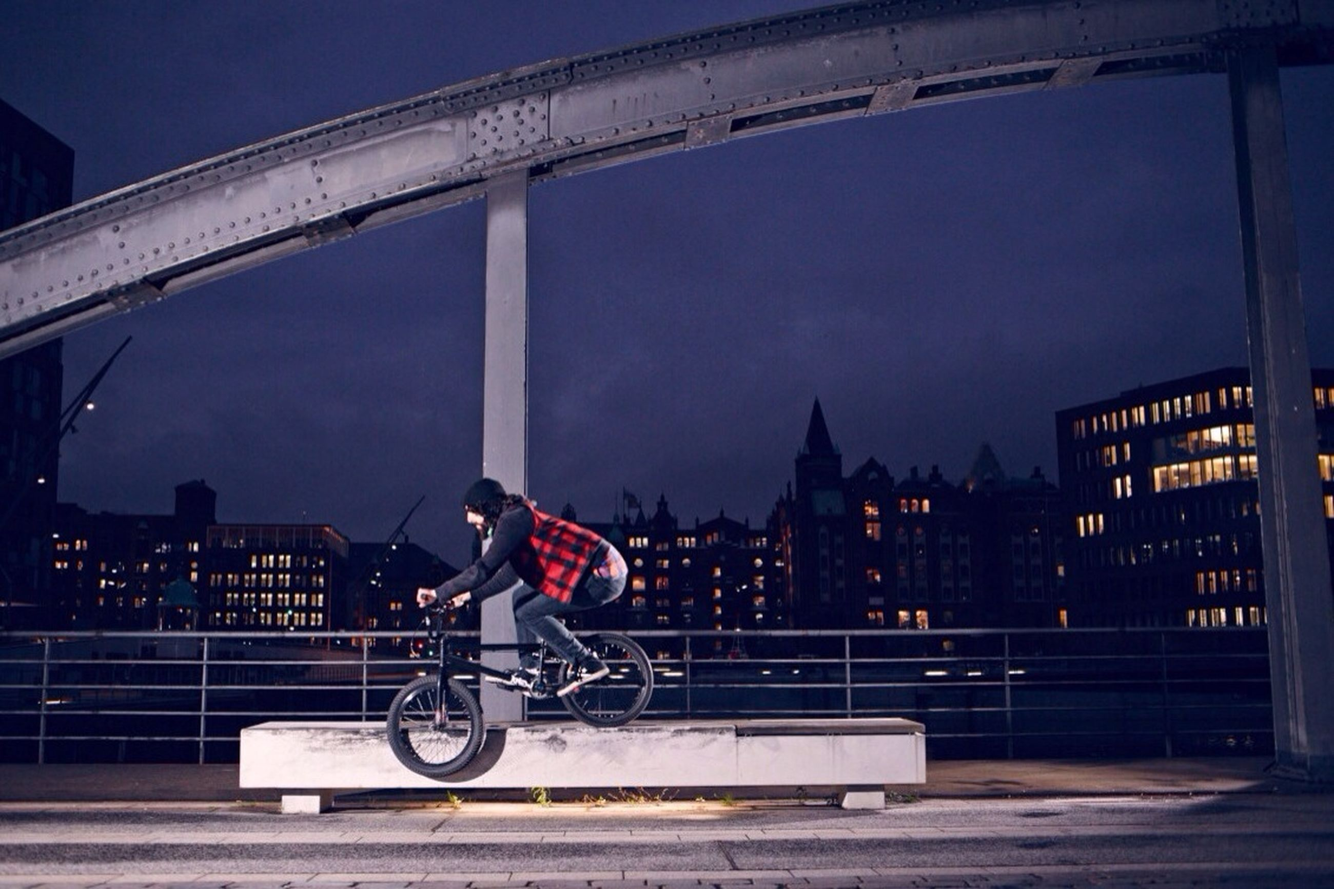 architecture, built structure, building exterior, transportation, bicycle, sky, railing, city, mode of transport, illuminated, full length, land vehicle, bridge - man made structure, lifestyles, men, connection, street, leisure activity